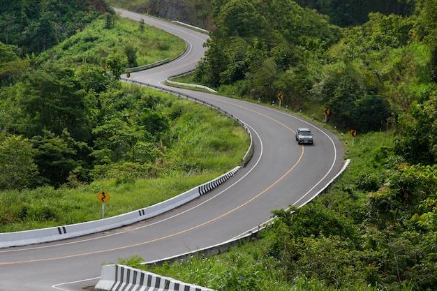 Gebogen asfaltweg met een auto in de bergen.