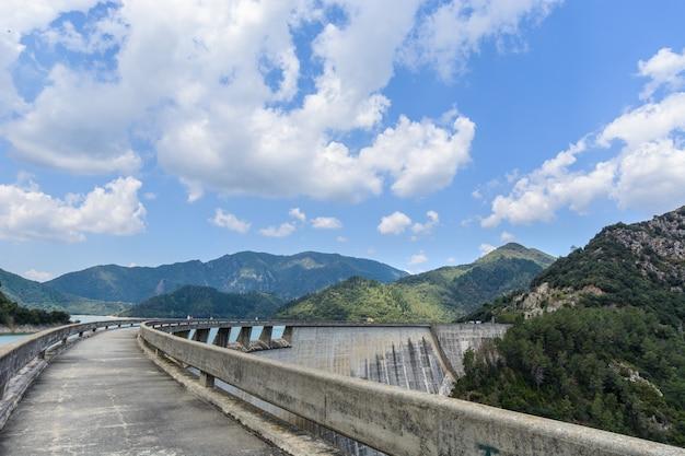 Gebogen damweg & bergen onder wolken