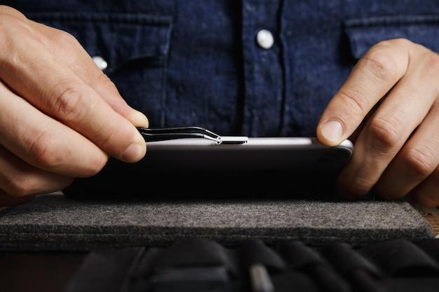 Gebogen esd-pincet die de microsimkaartlade uit de behuizing van de mobiele smartphone trekt in de buurt van de toolkit-tas