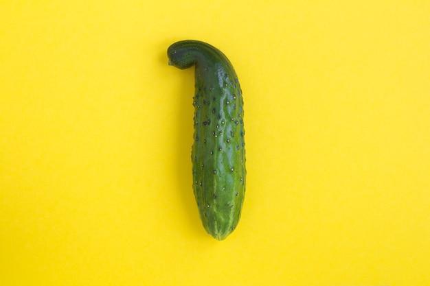 Gebogen komkommer in het midden van het gele oppervlak