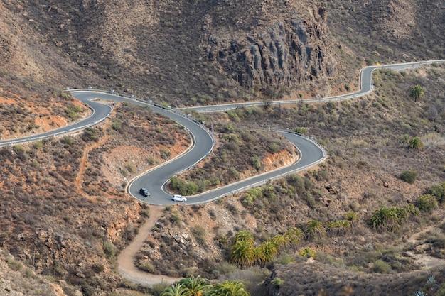 Gebogen kronkelende weg met twee auto's rijden in de bergen in gran canaria