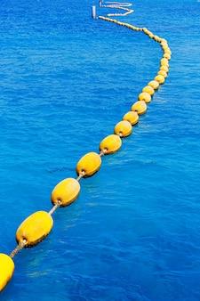 Gebogen lijn van gele boeien in helderblauwe zee