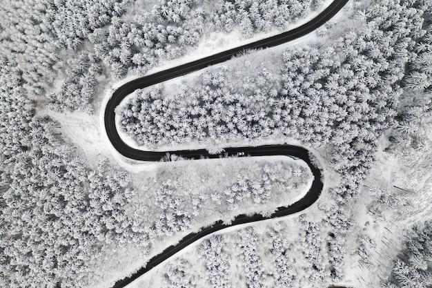 Gebogen s-vormige weg in de winter bos luchtfoto. lege kronkelende weg omgeven door hoge pijnbomen.