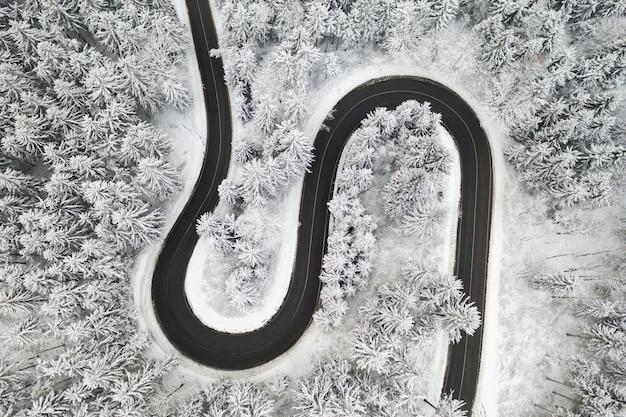 Gebogen s-vormige weg in de winter bos luchtfoto.