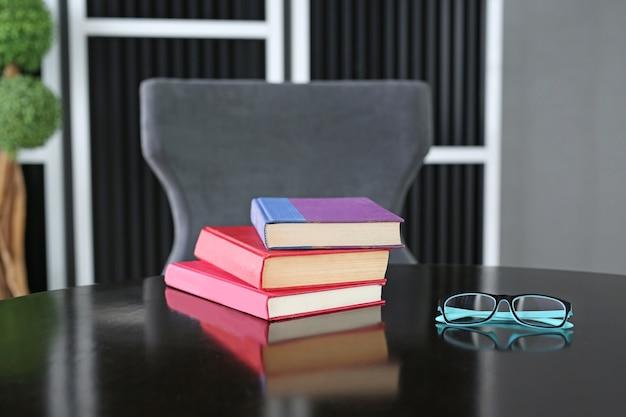 Gebonden boeken op houten tafel met een bril