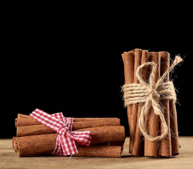Gebonden bos van bruine pijpjes kaneel op een bruine houten achtergrond, close-up