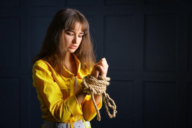 Gebonden met vrouw van de kabel de jonge vrouw gebonden handen in gevangenschap