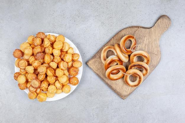 Gebonden ring van sushki op een houten bord naast een bord koekjes op marmeren oppervlak.