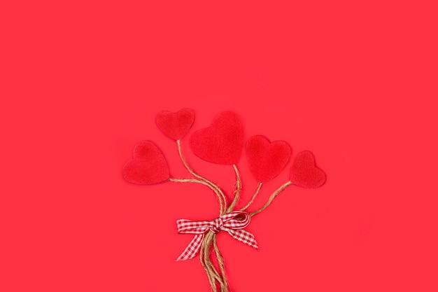 Gebonden rode papieren harten als ballons op een rode achtergrond