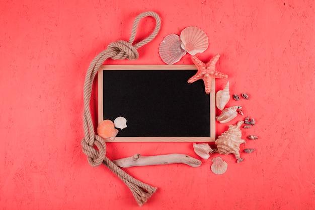 Gebonden touw; schelpen; hout met lege schoolbord op koraal geweven achtergrond