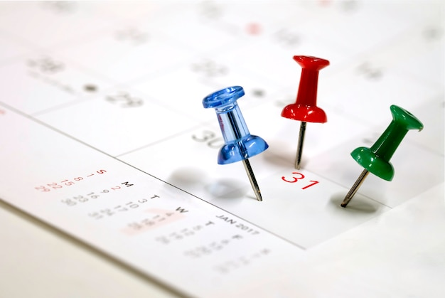 Geborduurde blauwe roodgroene pinnen op een kalender op de 31e met selectieve aandacht