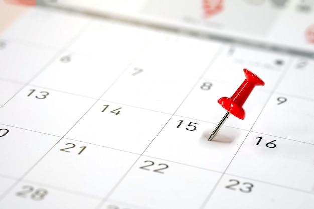 Geborduurde rode pinnen op een kalender op de 15e met selectieve focus