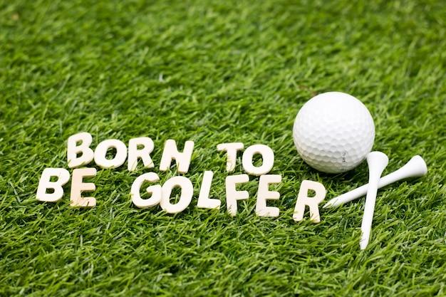 Geboren om golfspeler te zijn die groen gras met golfbal en t-stuk verwoordt