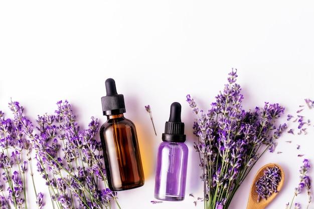 Gebotteld lavendel etherische olie en lavendel takjes op witte achtergrond met kopie ruimte, bovenaanzicht. kuuroordconcept.