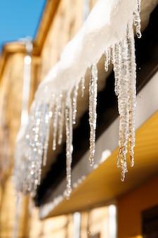 Gebouw bedekt met ijspegels in zonnige winterdag