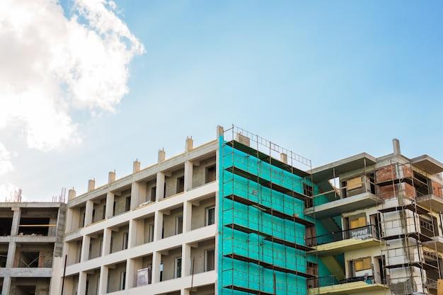 Gebouw en kranen in aanbouw tegen blauwe hemel.