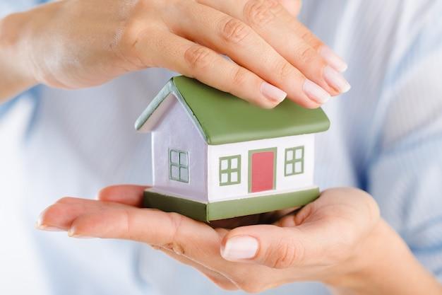 Gebouw, hypotheek, onroerend goed en onroerend goed concept - close-up van handen met huismodel
