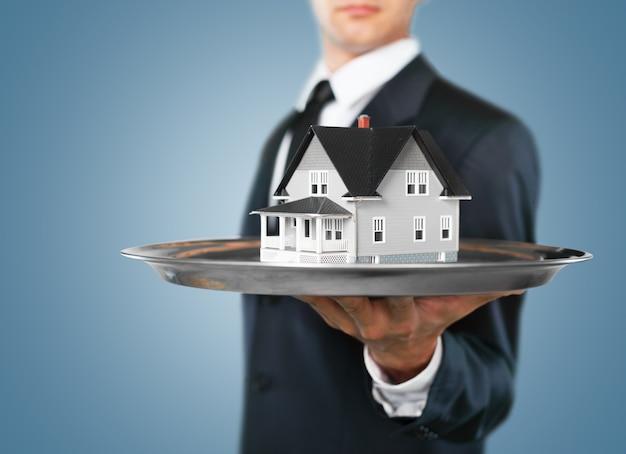 Gebouw, hypotheek, onroerend goed en onroerend goed concept - close-up van het huismodel van de hand