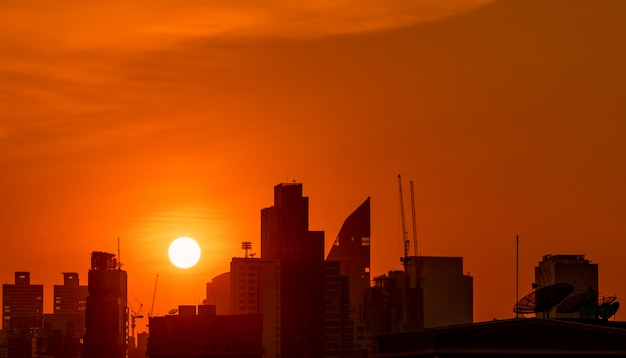 Gebouw in het centrum in de schemering met prachtige zonsondergang hemel. silhouet van condo en appartement in de avond. cityscape van wolkenkrabber bouwen en bouwen kraan.