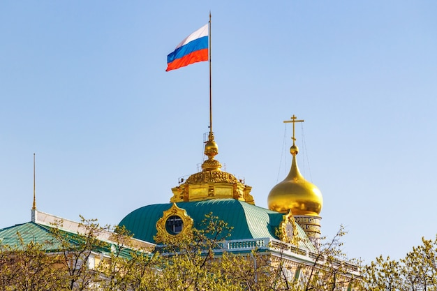 Gebouw van grand kremlin palace met russische federatie vlag zwaaien op het dak tegen gouden koepel van de kerk in zonnige ochtend