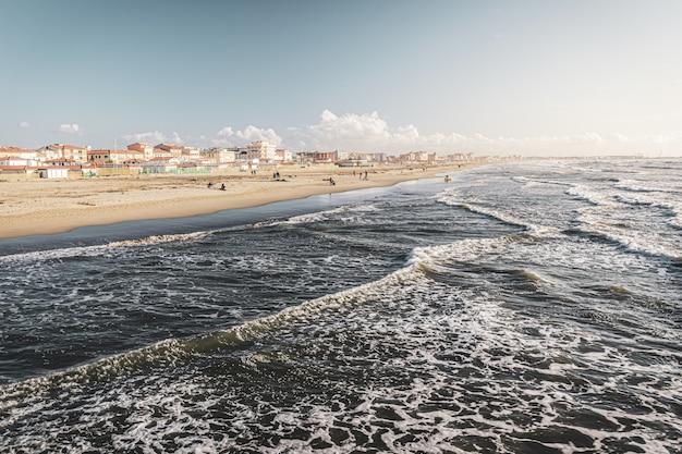 Gebouwen aan de kust in de buurt van gekke golven van de zee