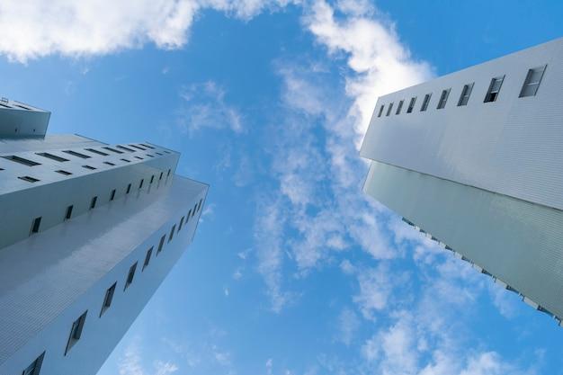 Gebouwen van onderaf gezien, met blauwe lucht en wolken.