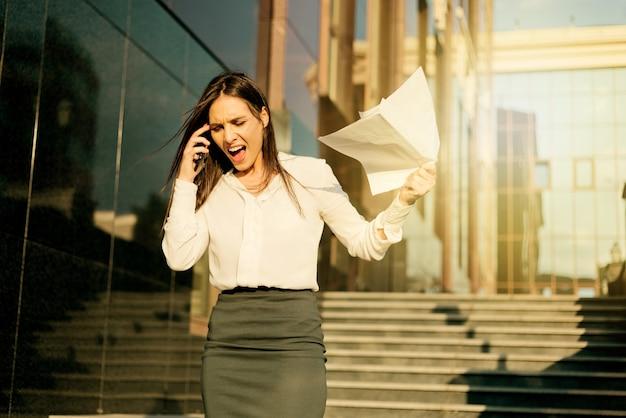 Gebracht tot hysterie, boze zakenvrouw gekleed in een witte blouse en rok, schreeuwend in de telefoon, gooit vellen papier buiten in de stad