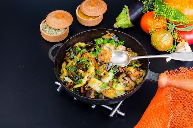 Gebraden aubergine, paprika en verschillende groenten in pan op zwarte achtergrond
