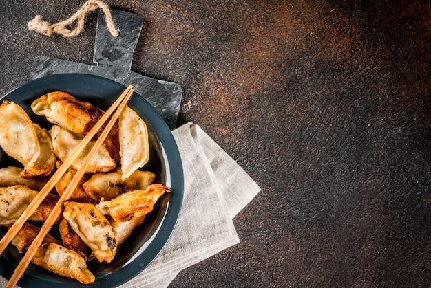 Gebraden aziatische bollen gyoza op donkere plaat, die met eetstokjes en sojasaus, donkere achtergrond, exemplaarruimte wordt gediend