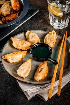 Gebraden aziatische bollen gyoza op donkere plaat die met eetstokjes en sojasaus wordt gediend