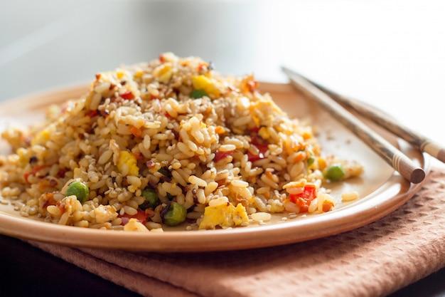 Gebraden chinese rijst met dicht omhoog groenten en eieren met eetstokjes