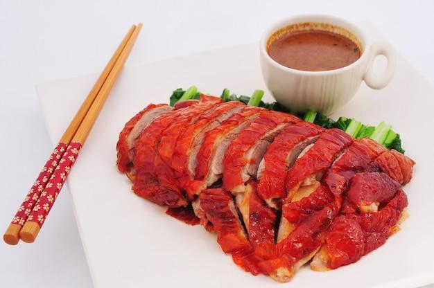 Gebraden eend gesneden porties op plaat met saus chinese keuken
