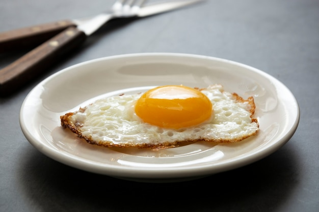 Gebraden ei dicht omhoog in witte plaat. ontbijt. zonnige kant zacht gebakken ei.