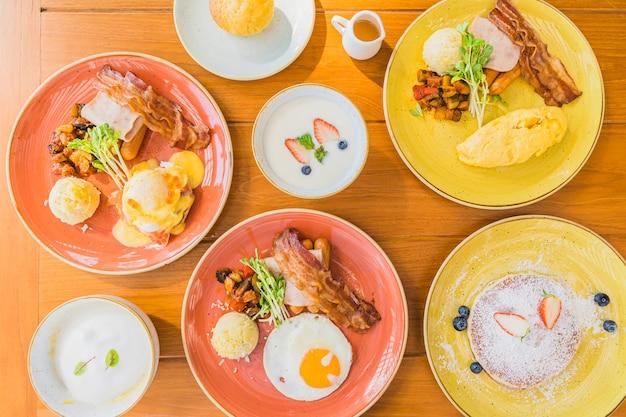 Gebraden ei met eieren benedict en omelet rond bacaon hamworst in plaat