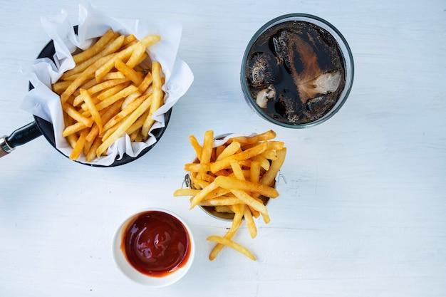 Gebraden frieten en ketchup met frisdranken op een lijst