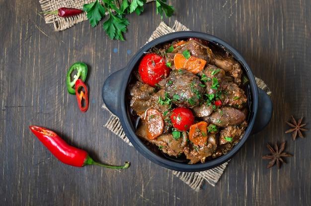 Gebraden kalkoenlever met groenten in een pot. heerlijke dieetmaaltijd. rustieke stijl. bovenaanzicht, plat gelegd.