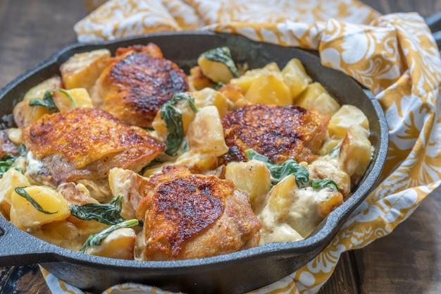 Gebraden kip, aardappelen en spinazie met roomsaus in een koekenpan