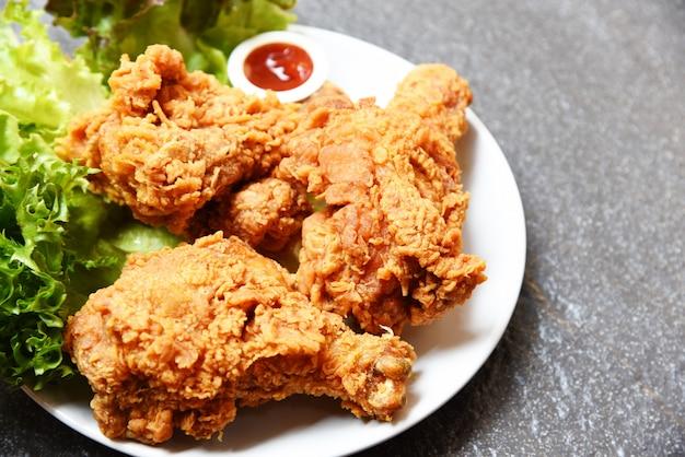 Gebraden kip knapperig op witte plaat met ketchup en saladeslagroente op donkere plaat