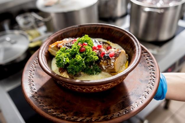 Gebraden kip met aardappel en groenten op fornuis. keuken