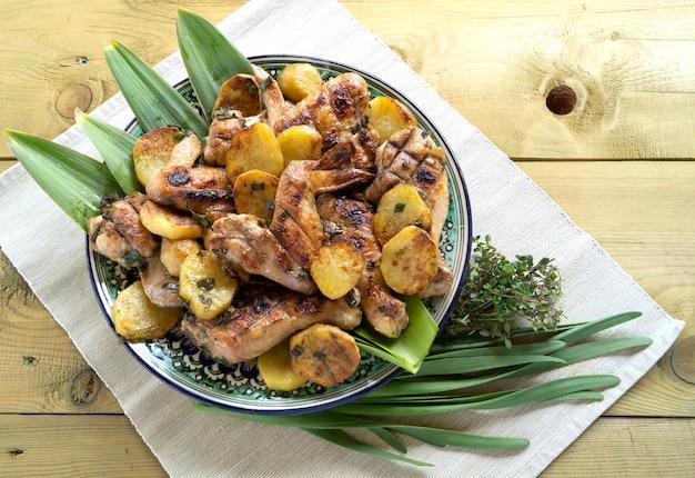 Gebraden kippentrommels met aardappels, rozemarijn en kruiden.