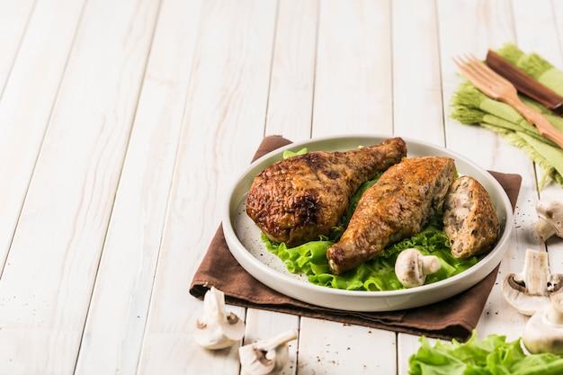 Gebraden kippentrommelstok die met paddestoelen vlakke plaat wordt gevuld met slablad op licht hout.