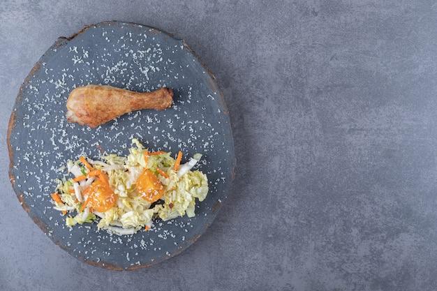 Gebraden kippentrommelstok en salade op houten stuk.
