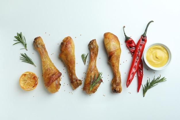 Gebraden kippentrommelstokken en ingrediënten op witte achtergrond