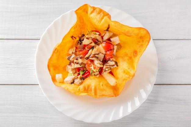 Gebraden kippenvlees met tomaten en saus in pitabroodje op witte houten lijst.