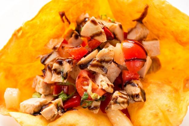 Gebraden kippenvlees met tomaten en saus in pitabroodje.