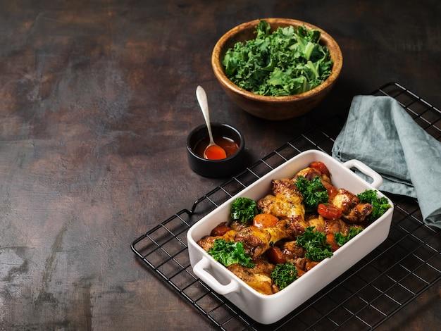 Gebraden kippenvleugels met worteltjes, boerenkool, knoflook en dipsaus.