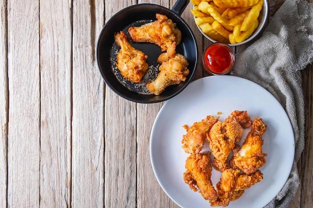 Gebraden kippenvoedsel en frieten op een houten lijst