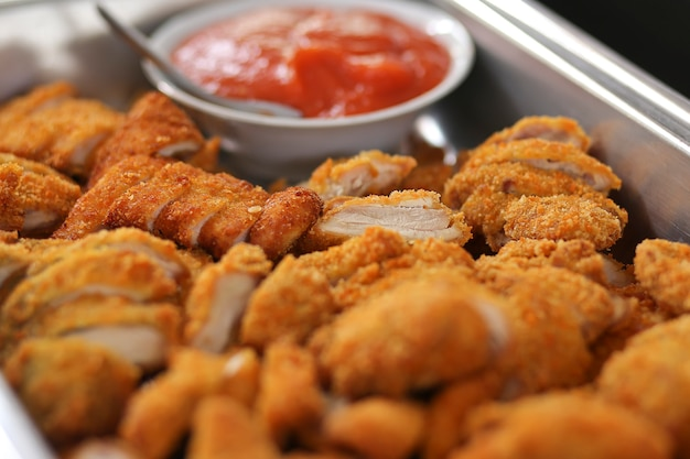 Gebraden knapperige kippengoudklompjes met frieten en ketchup op witte raad