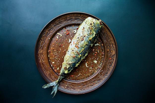 Gebraden makreel op een plaat, donkere achtergrond.