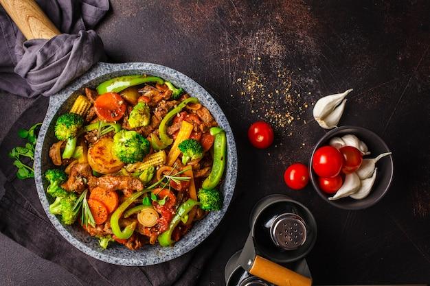 Gebraden rundvleesstroganoff met aardappels en groenten in een pan, hoogste mening.